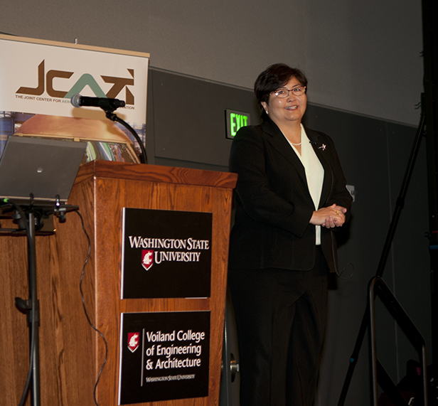 Iris Fujiura Bombelyn standing next to a podium in front of a JCATI banner.