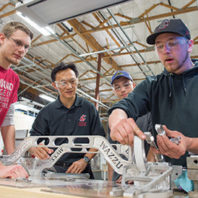 Xiaopeng Bi and WSU Everett students working on their Mars rover chassis suspension system.