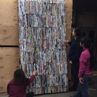WSU students look at their pixlr wall made from rolled up magazine pages.