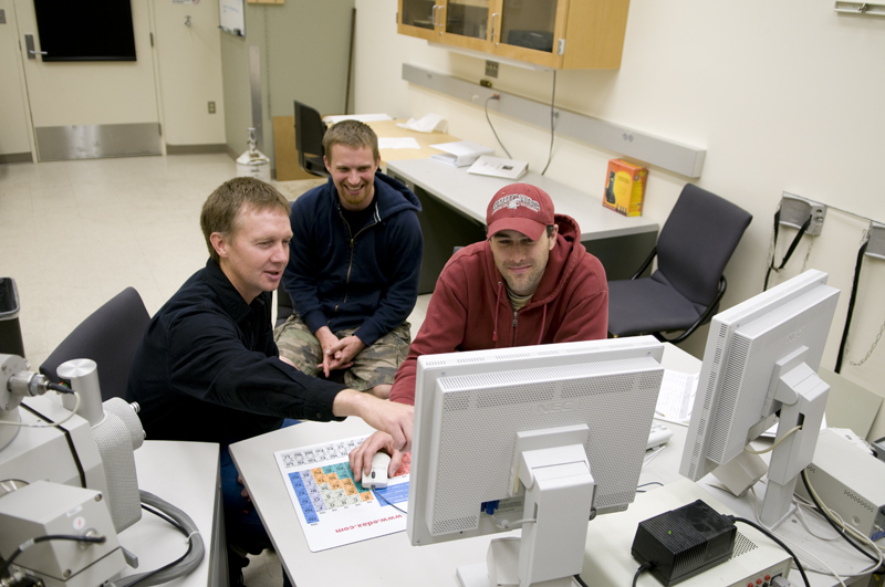 Dave Field and two students seated in front of computer screens.