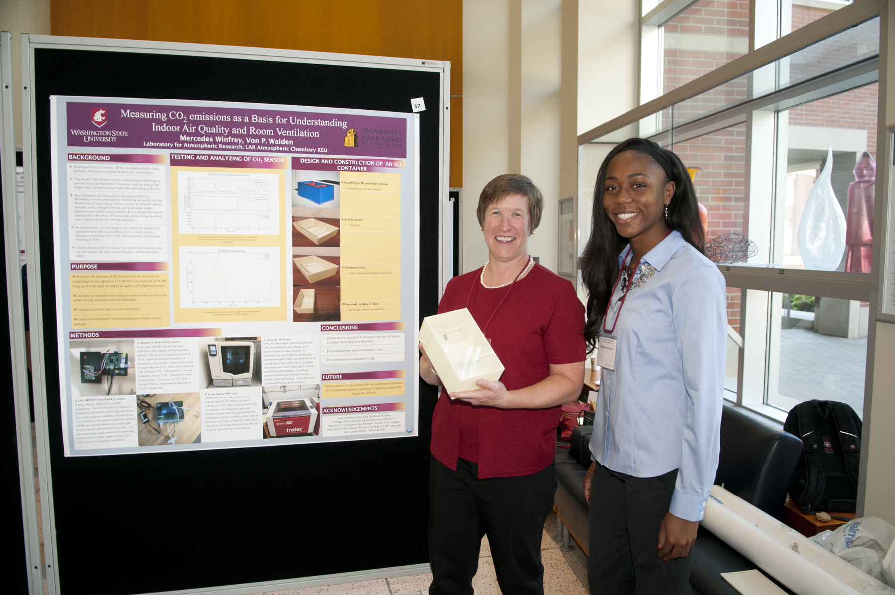 Shelley Pressley and Mercedes Winfrey pose next to a research poster.