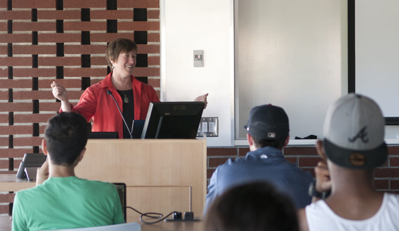 Shelly Pressley standing at a podium during a class lecture.