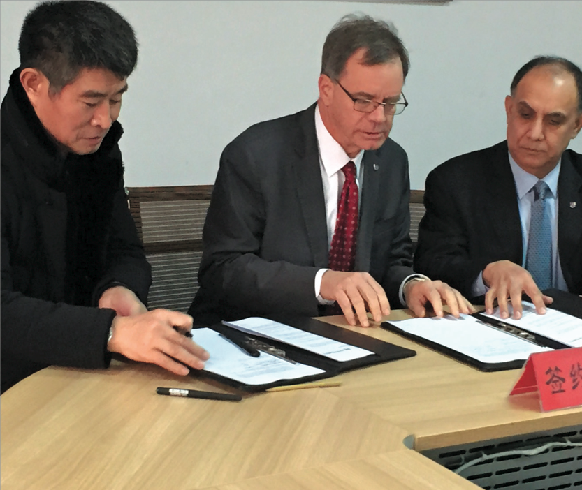 Yunsheng Ma, chairman of Shandong Chambroad Holding Co. Ltd., left, and WSU's Chris Keane and Asif Chaudhry sign the agreement in China.