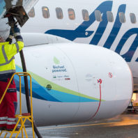 Jared Svraka stands on a step ladder to fuel an Alaska Airlines plane.