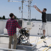 Students Nathan Sparks and Brandon Daub adjust sensors on a rooftop.