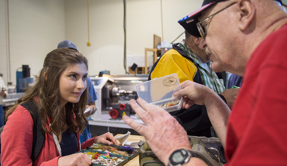 Matese Stevens holds a box of fishing flies and listens to the veteran teaching her.