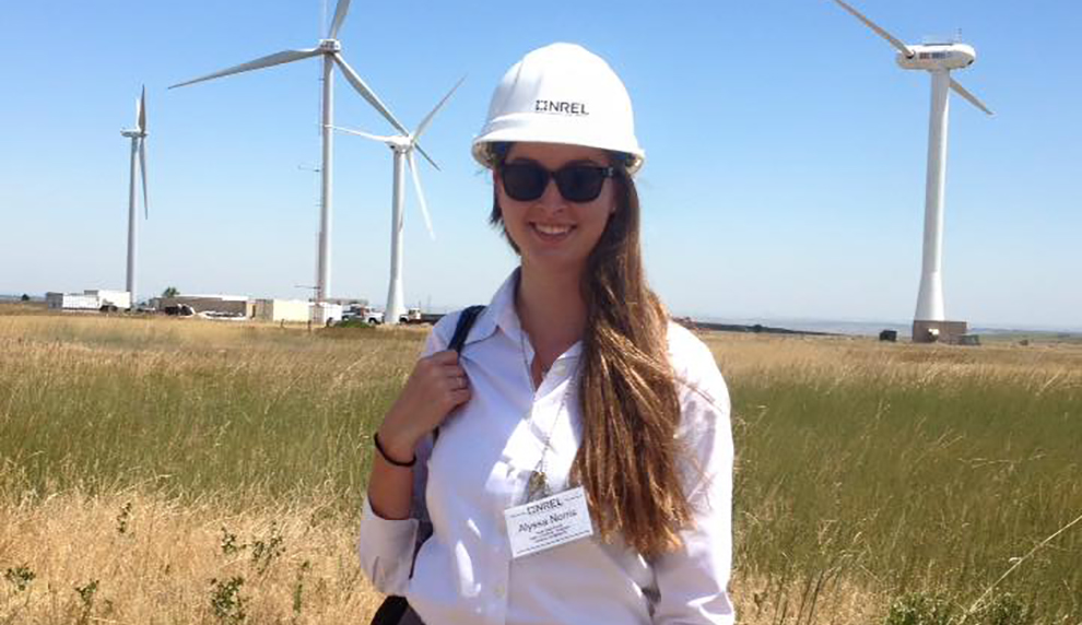 Alyssa Norris standing near wind turbines.
