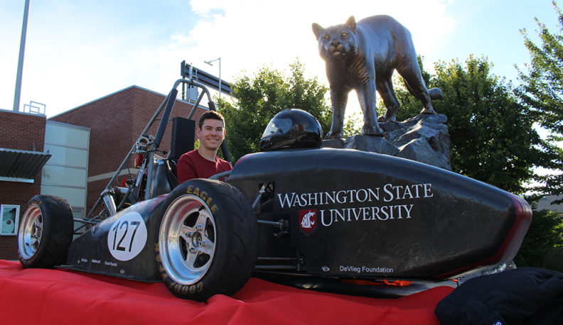 Kory O'Connor sits in WSU's Formula SAE race car next to WSU's bronze cougar statue.