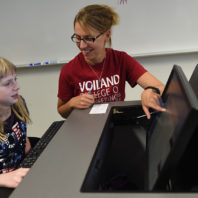 Gina Sprint helps a Cougar Quest participant write code at a computer.