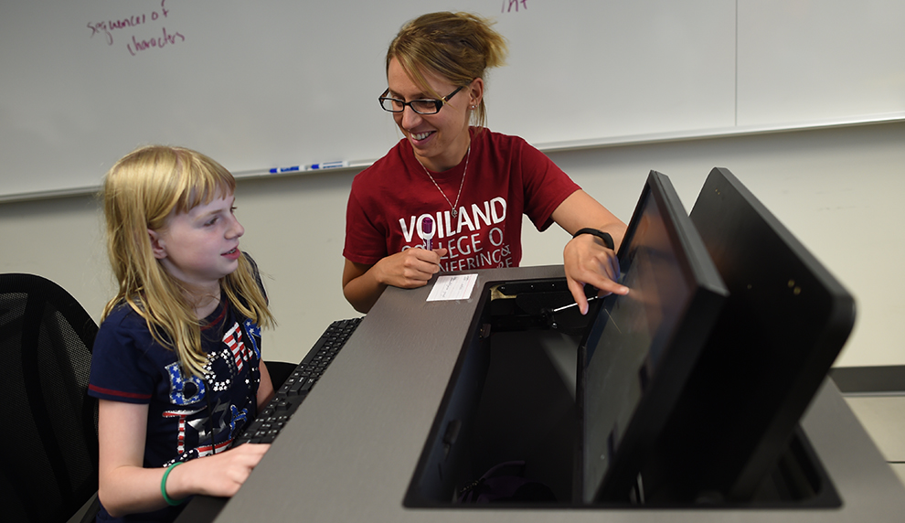 Gina Sprint helping a Cougar Quest participant write code at a computer.