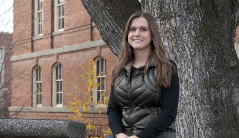 Samantha McNicholas sitting by a tree.