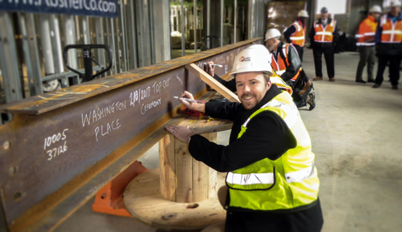 Bernt Johnson writes on a beam at the construction site of Washington Place.