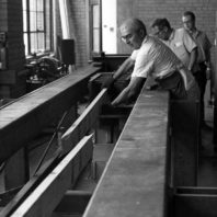 Researcher moving a broken board in the wood lab circa 1960.