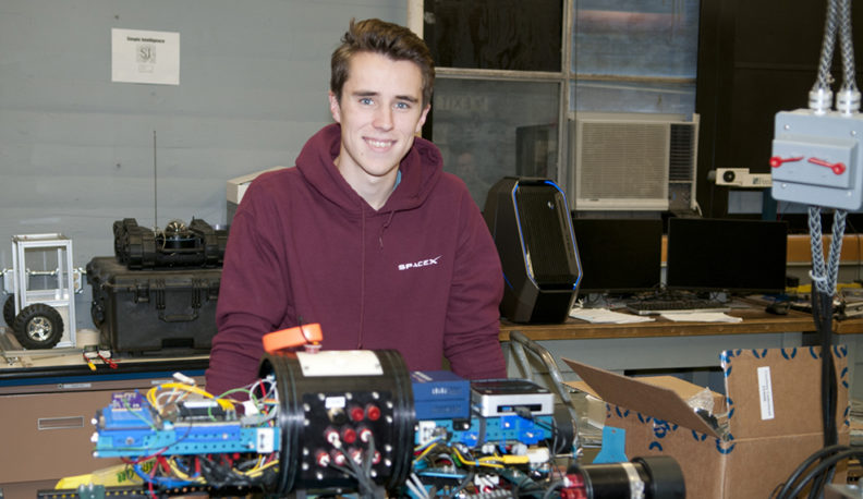 Ryan Summers poses in a lab with the Robosub.