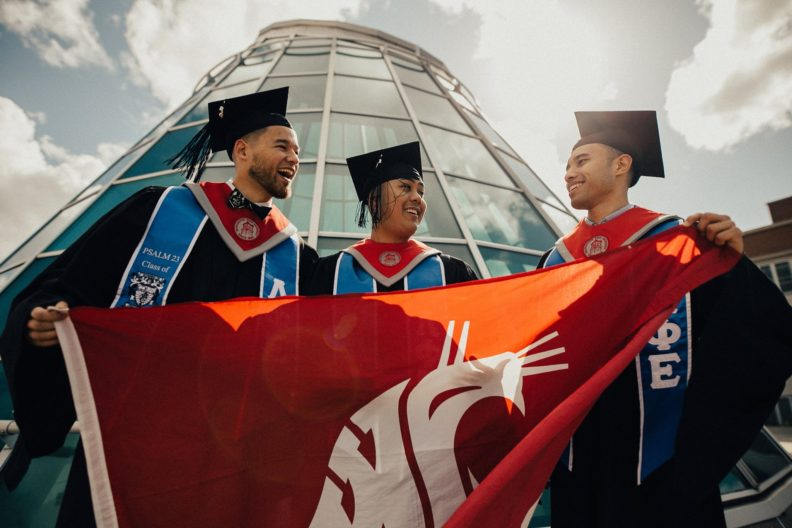Three WSU students wearing caps and gowns and holding a Cougar flag.