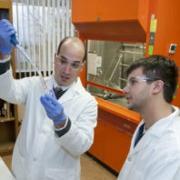 Steven works with a student in the lab.
