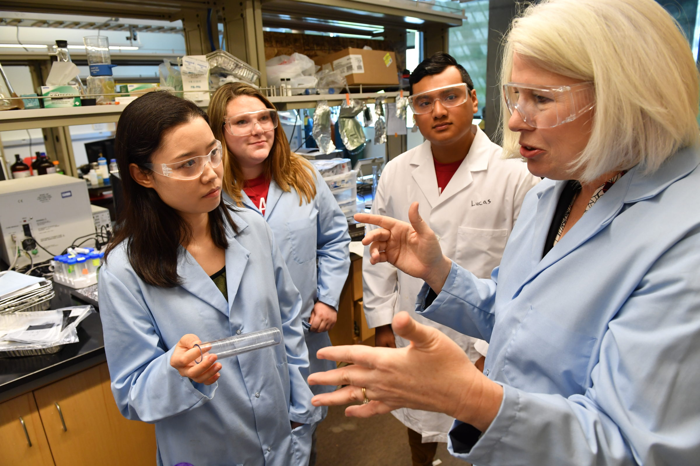 Mary Rezac and students in a lab wearing lab coats and safety glasses.