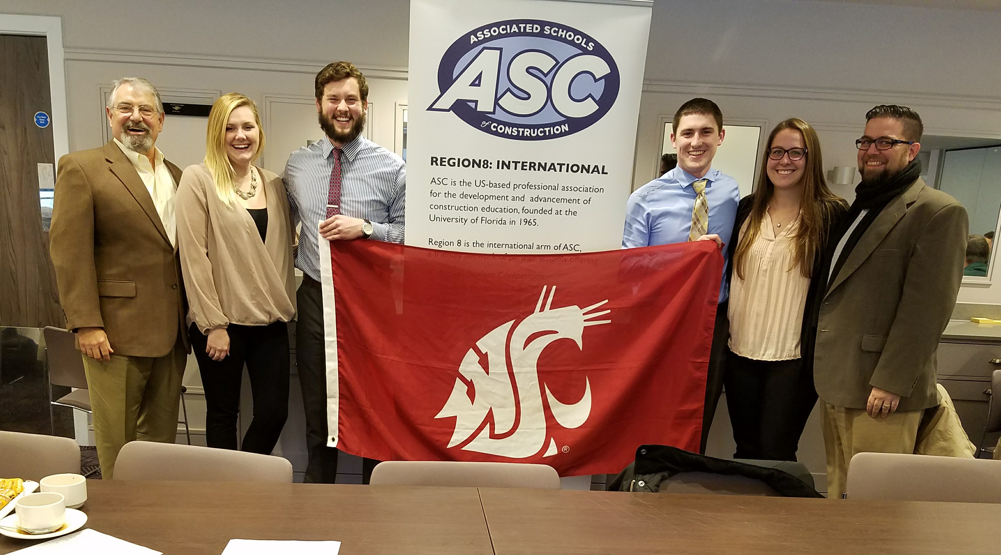 Jason Peschel and Dr. David Gunderson with four students, holding the WSU flag. Students were participating in the ASC Regional Competition.