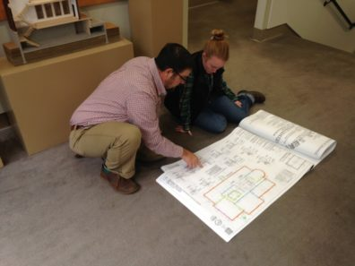 Peschel rolls out construction plans on the floor as he works with a student.