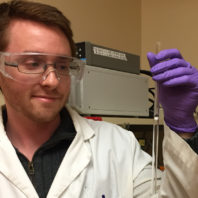 Jake Gray holds up catalyst in the lab.