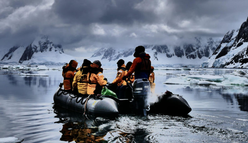 A small group of researchers are sitting in a motorboat that is traveling down icy waters.