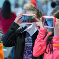 Three young girls looking through virtual reality goggles.