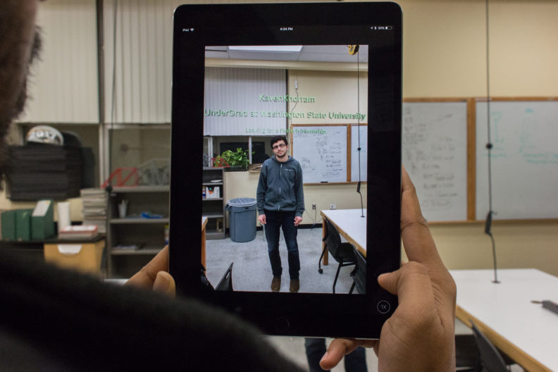 Person is holding an iPad up with Kaveh in the camera being scanned by the app.