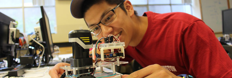 Student working on a small robot in the Frank Innovation Zone.