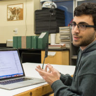 Kaveh Khorram sits at his laptop during an interview