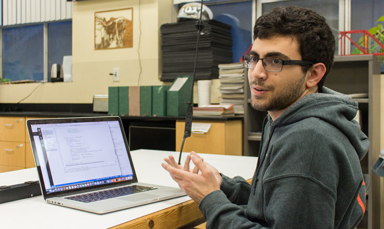 Kaveh Khorram sits at his laptop during an interview.