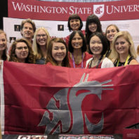 Women engineers posing with the WSU cougar flag at the Grace Hopper Convention.