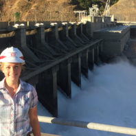 Paige Danielson wearing a hard hat and standing near a dam.