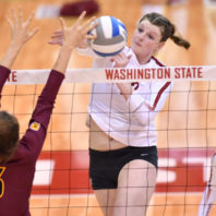Claire Martin spikes the volleyball over the net as an opponent tries to block.