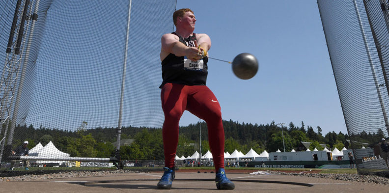 Action shot of Brock Eager swinging the metal ball during a hammer throw competition.