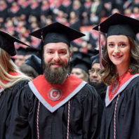 Dan Richer and Kelley Sindelar wearing graduation caps and gowns at WSU's 2018 Fall Commencement.