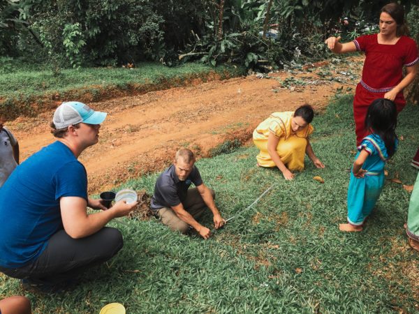 Three engineers check a water line while a young girl watches.