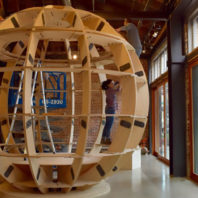 Miyasaka working on a giant wooden spherical sculpture.
