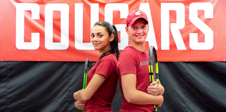 Student athletes Gizem Melisa Ates and Michaela Bayerlova pose back to back on the tennis court.