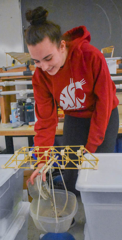 Woman pouring gravel into a bucket suspended from a model truss bridge built from fettuccine pasta.