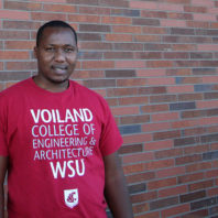 Peter Mugo stands in front of a brick wall wearing a Voiland College t-shirt.