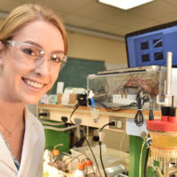 Roslyn VanSickle seated at a lab station wearing a lab coat and safety glasses.