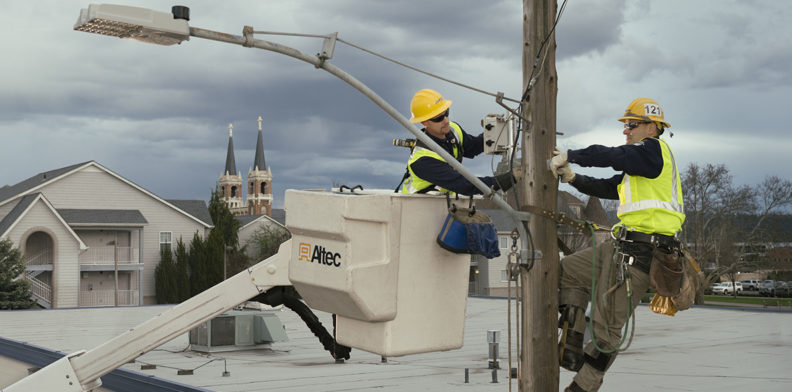 Lineman in aerial bucket assists pole-climbing lineman with installing sensors on light pole.