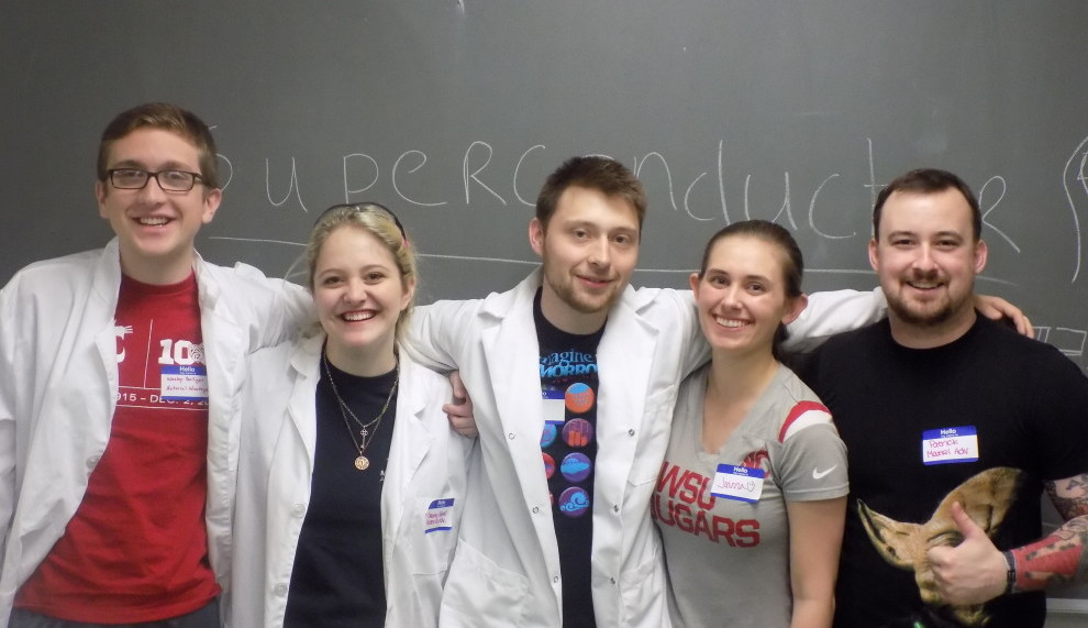 Five students standing in a row with arms around each other's shoulders.