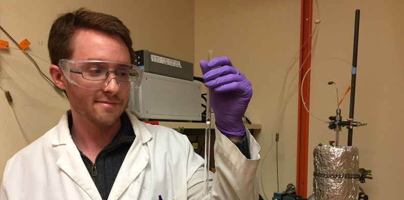 Voiland College student Jake Gray holds a catalyst up for the camera in a lab.