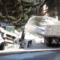 Bobcat utility vehicle blowing snow into the back of a dump truck to remove snow from the WSU Pullman campus.