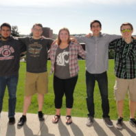 Five students standing in a row with their arms around each other's shoulders.