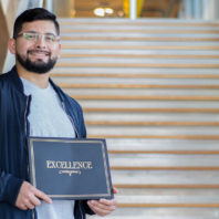 Yoni Rodriguez standing on stairs holding a certificate of excellence.