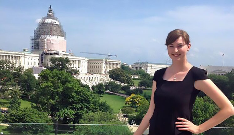 Alyssa Norris posing with United States Capitol under construction in the background.