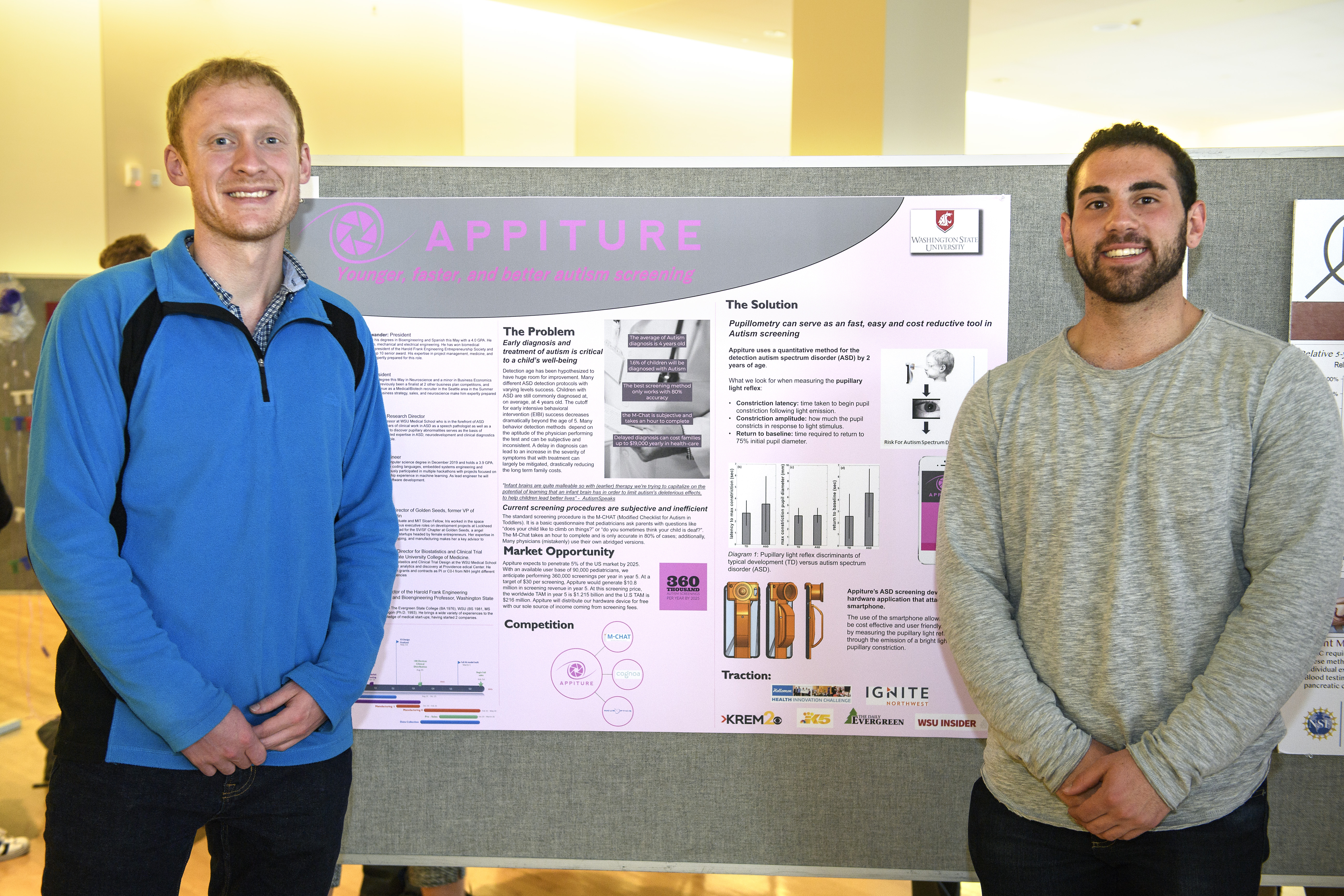 Lars Neuenschwander and TJ Goble standing in front of a poster describing their autism-detection app.
