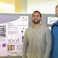 Lars Neuenschwander and TJ Goble standing beside a poster describing their autism-detection app.